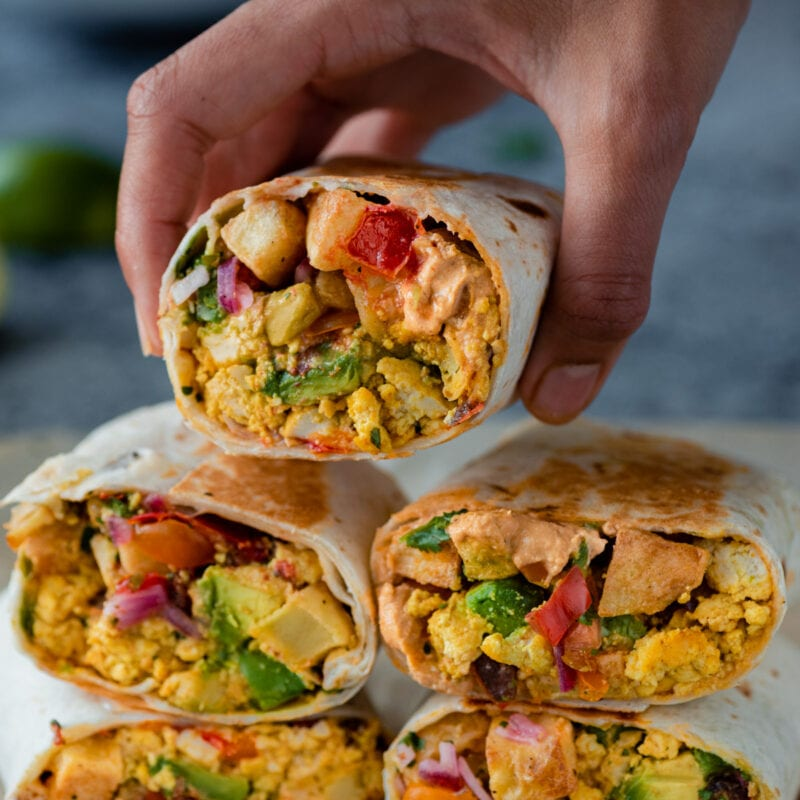 woman holding a vegan breakfast burrito over a stack of burritos