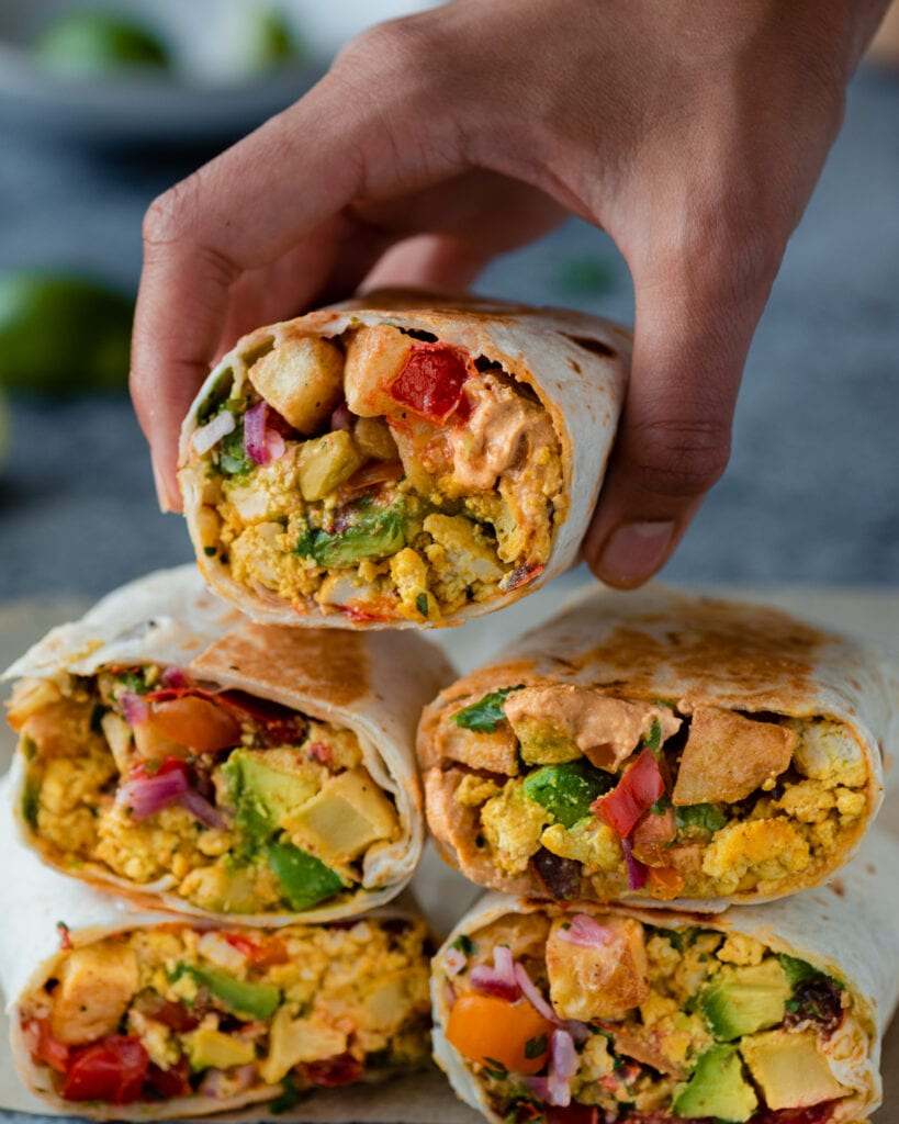 woman's hands holding a vegan breakfast burrito over a stack of burritos