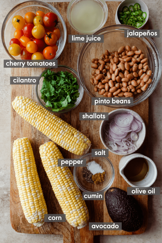 ingredients for grilled corn salad on cutting board with ingredient names labeled