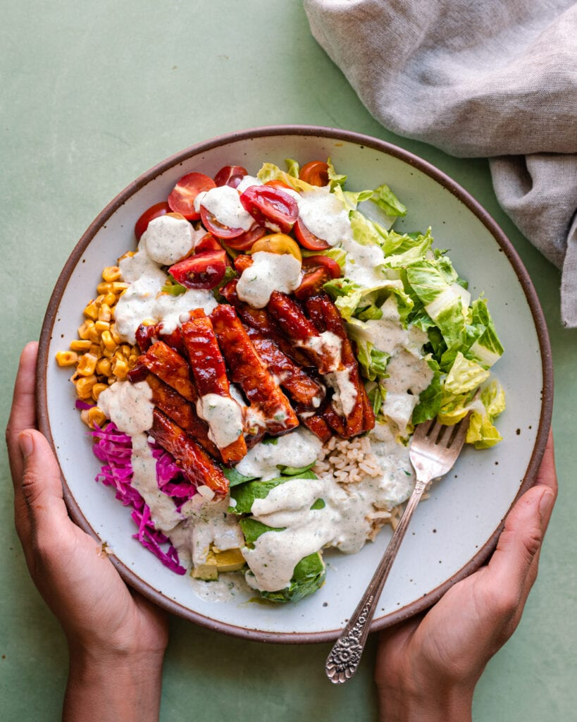 woman's hands holding white bowl of bbq tempeh bowl