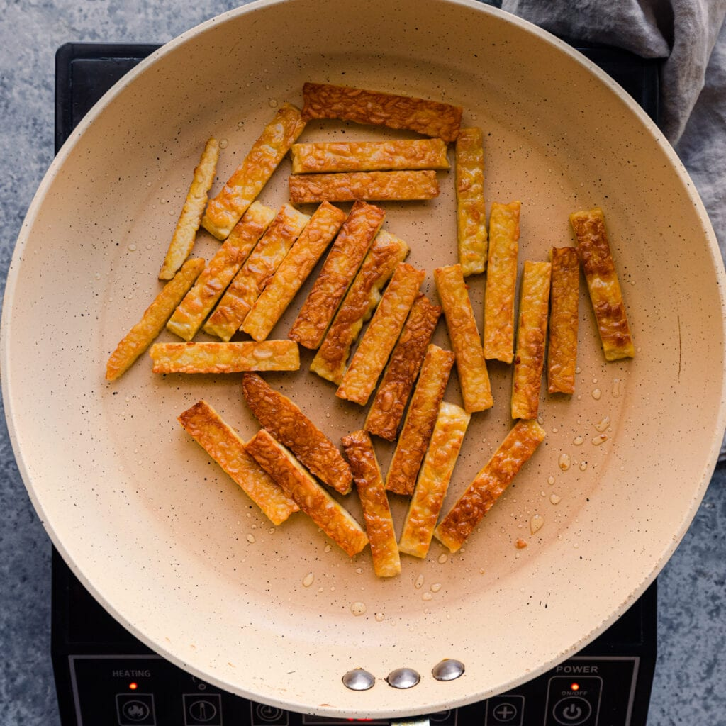 golden brown tempeh being cooked in frying pan