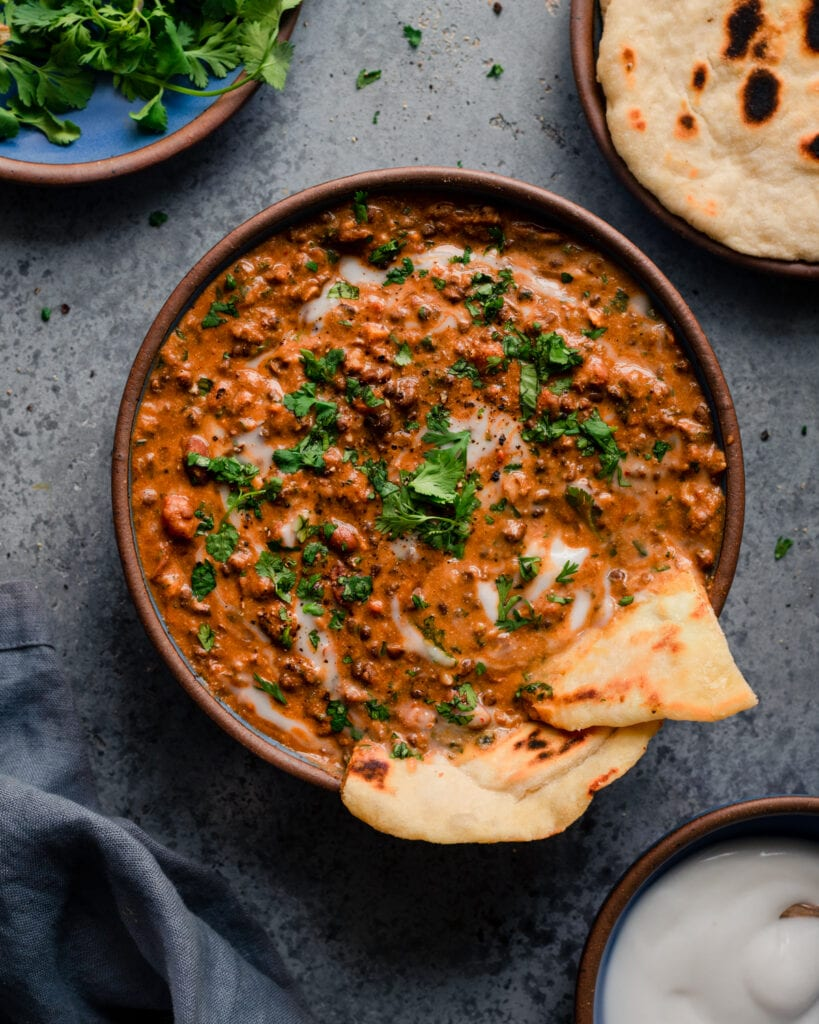 bowl of creamy vegan dal makhani with naan, yogurt, and cilantro on blue background
