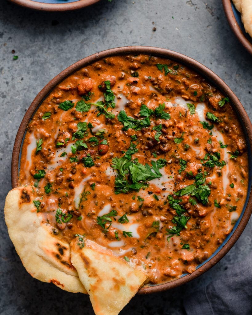 bowl of creamy vegan dal makhani with naan on blue background
