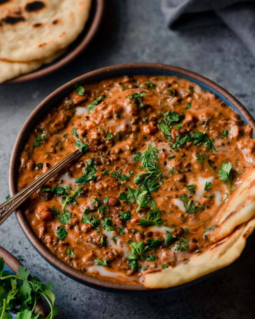 closeup bowl of creamy vegan dal makhani with spoon and naan on blue background