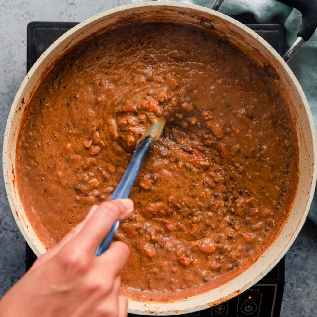 stirring a creamy pan of vegan dal makhani