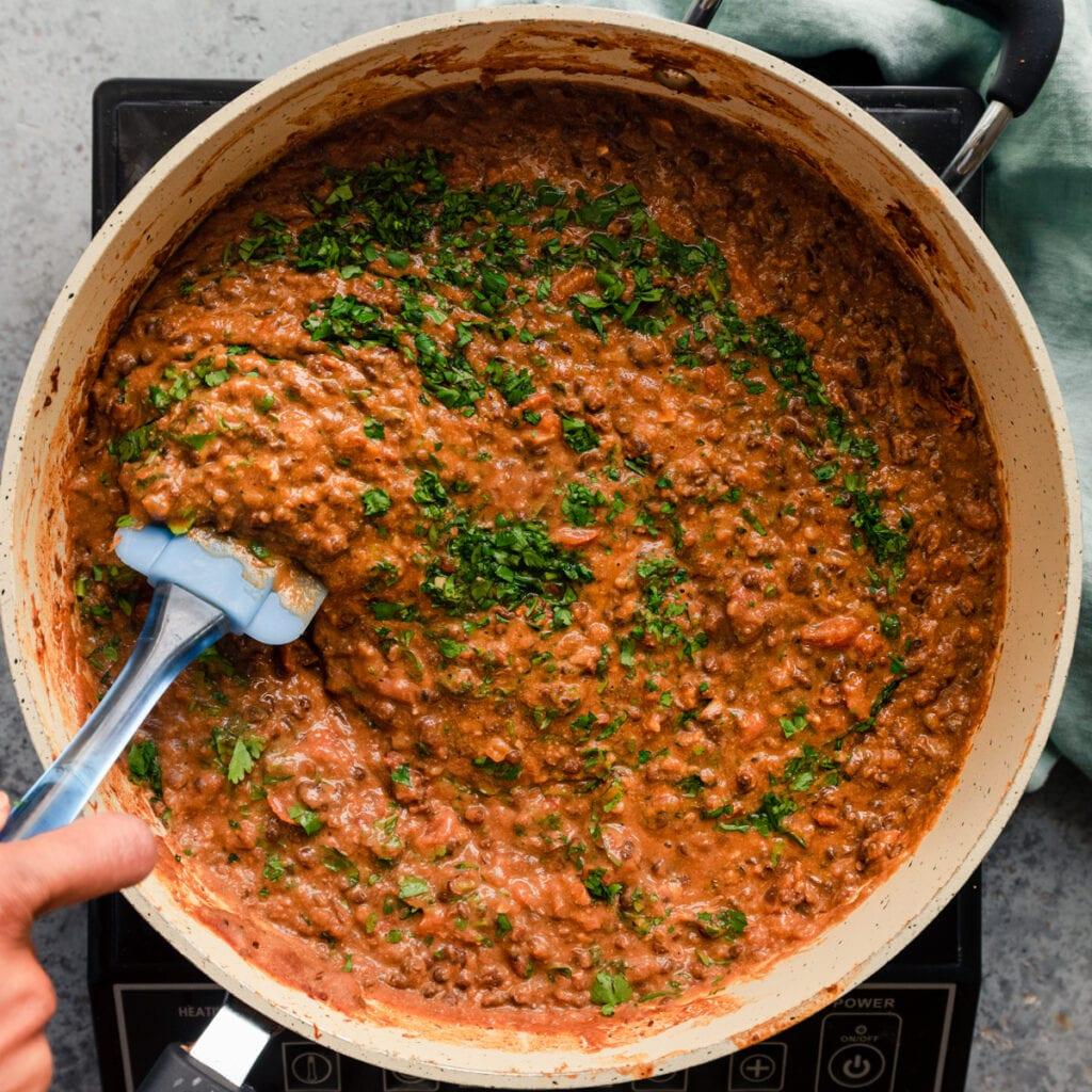 stirring cilantro into vegan dal makhani in saute pan