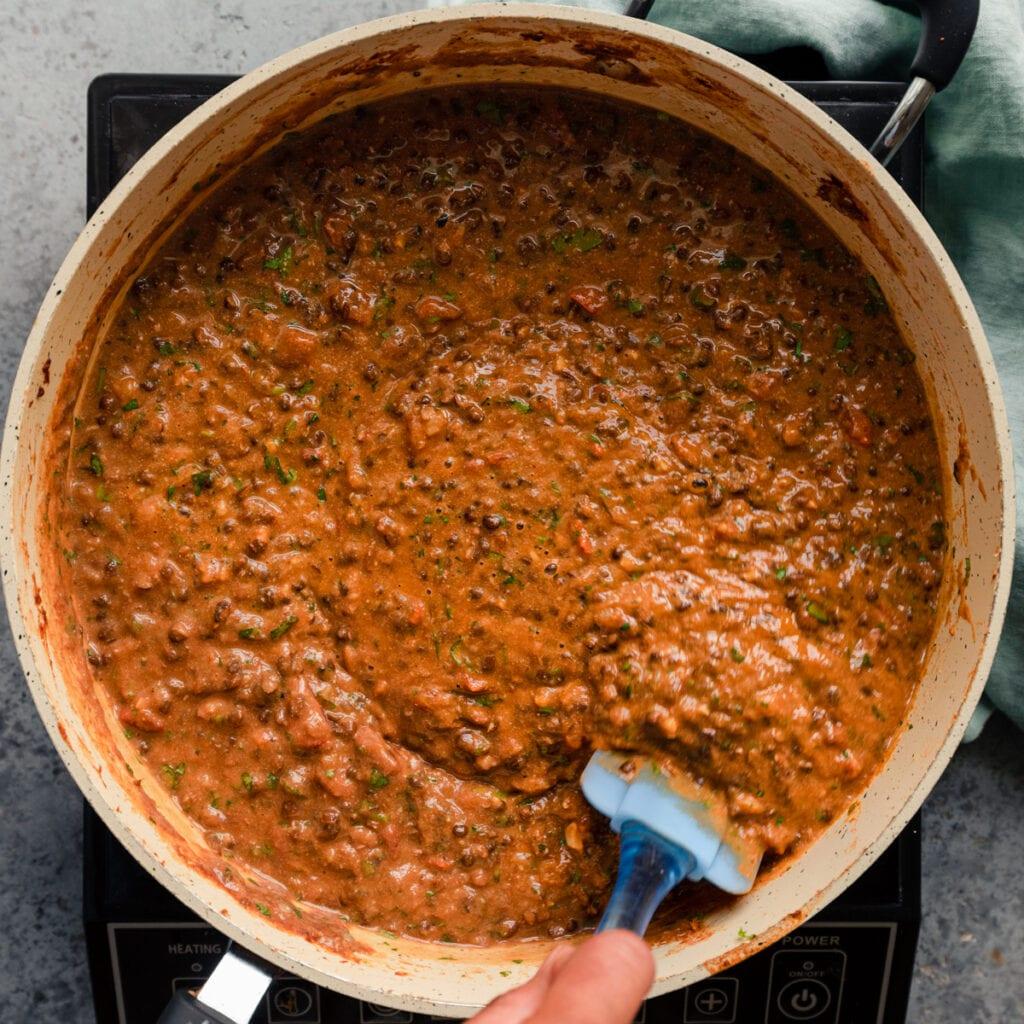 stirring creamy vegan Indian lentils in a saute pan