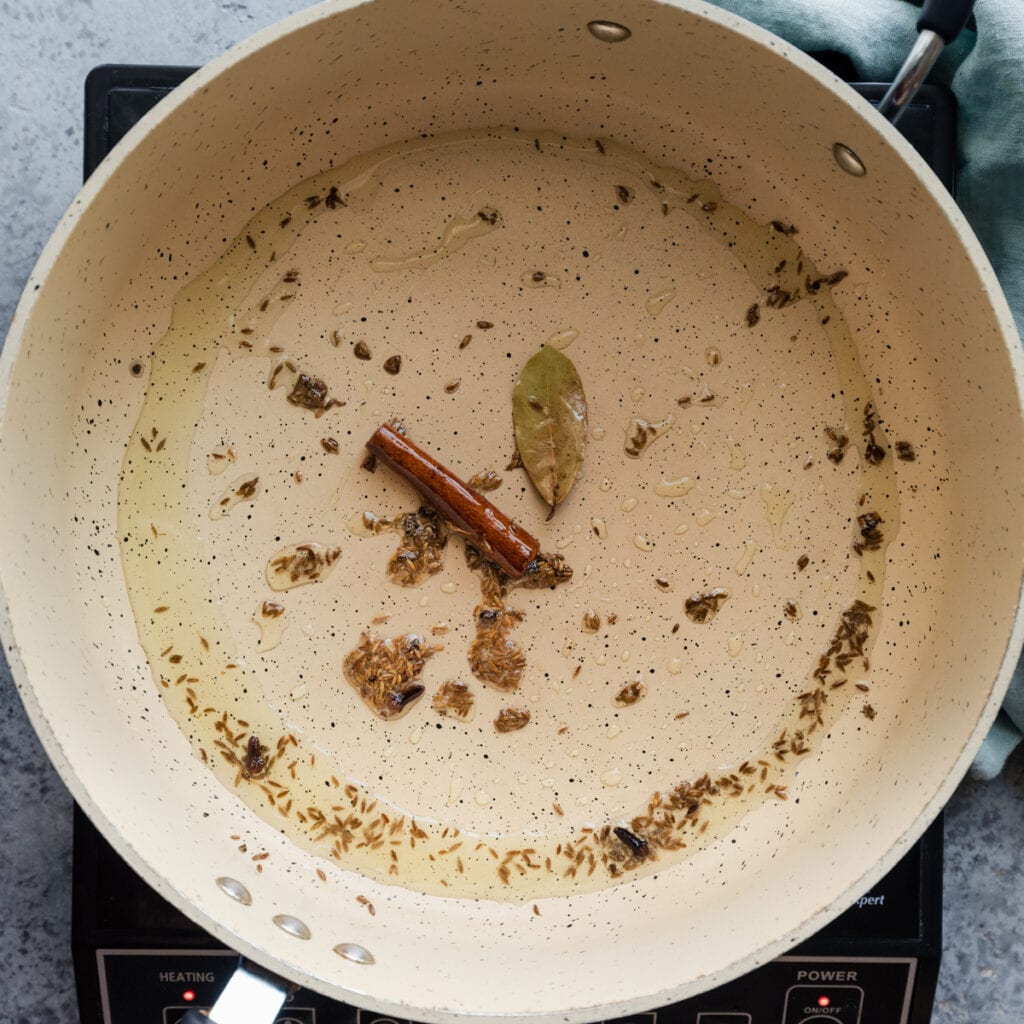 cooking whole spices in oil in a frying pan