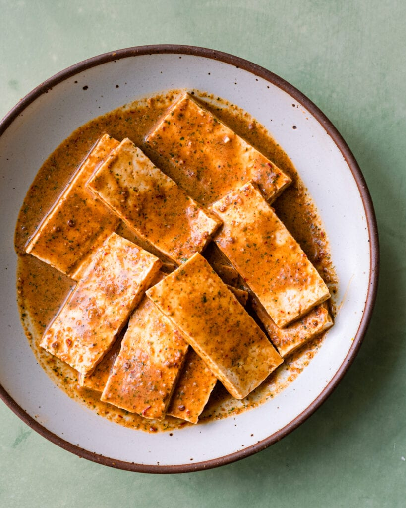 tofu marinating in citrus sauce in a white bowl