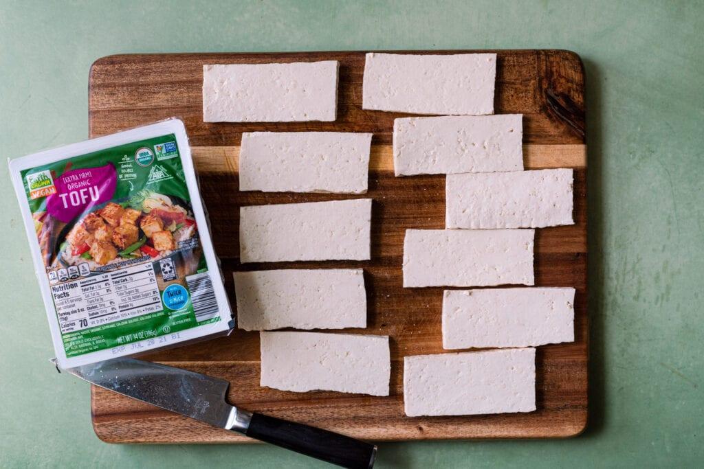 slabs of organic tofu on a wooden cutting board