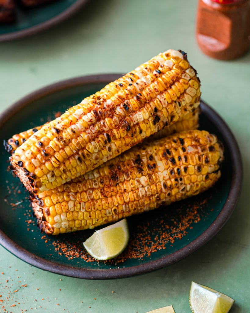 grilled corn with chili-lime seasoning on a green plate