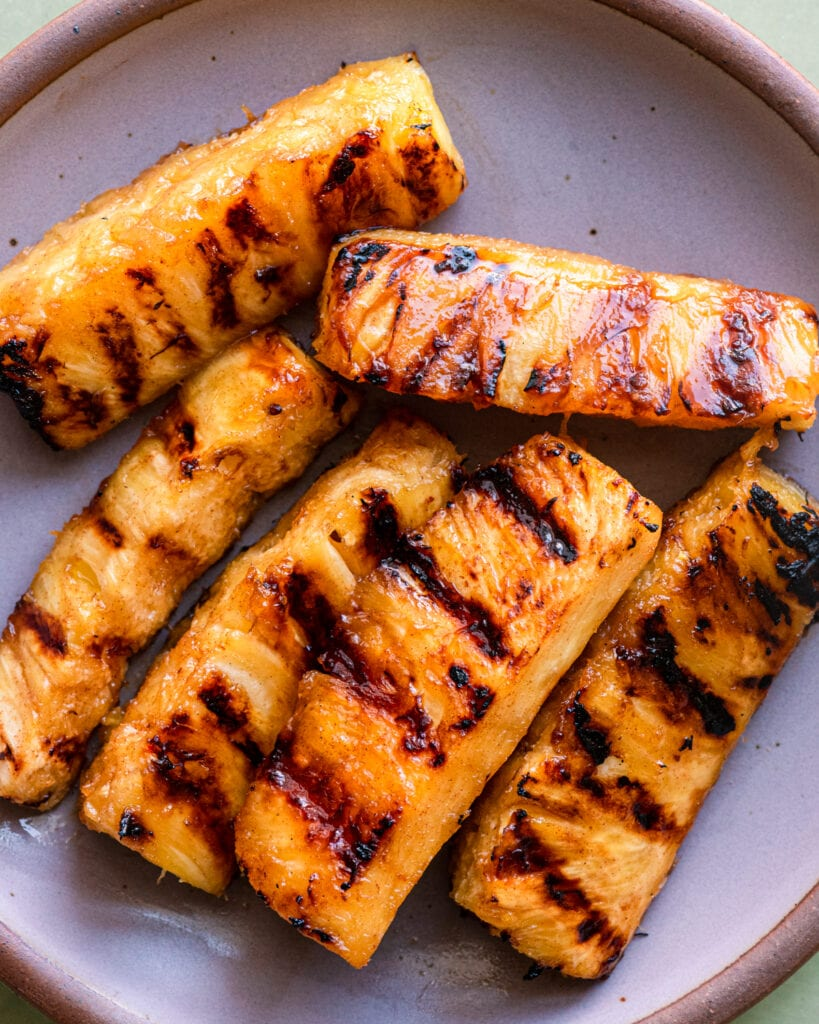 grilled pineapple spears on lavendar plate