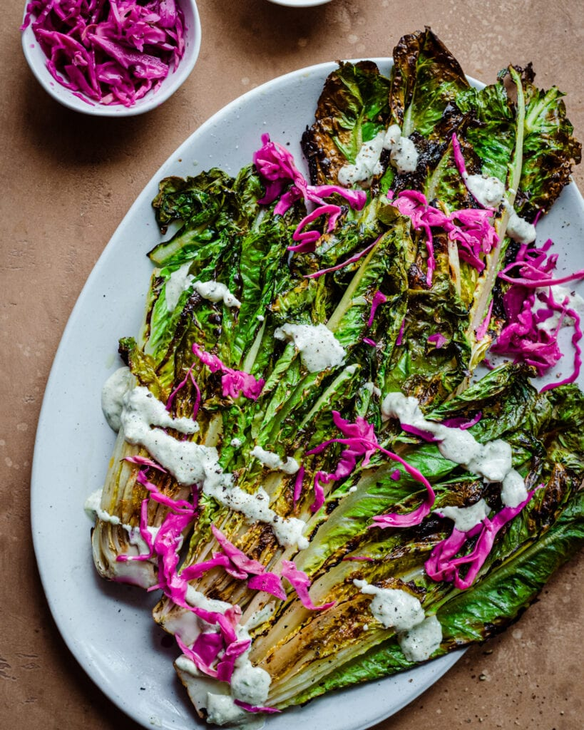 grilled romaine salad with creamy cashew dressing on pickled cabbage