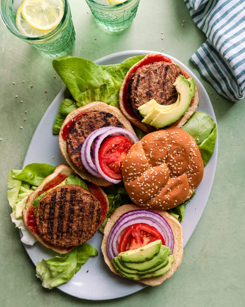 grilled vegan veggie burgers with burger buns, tomato, lettuce, and infused water