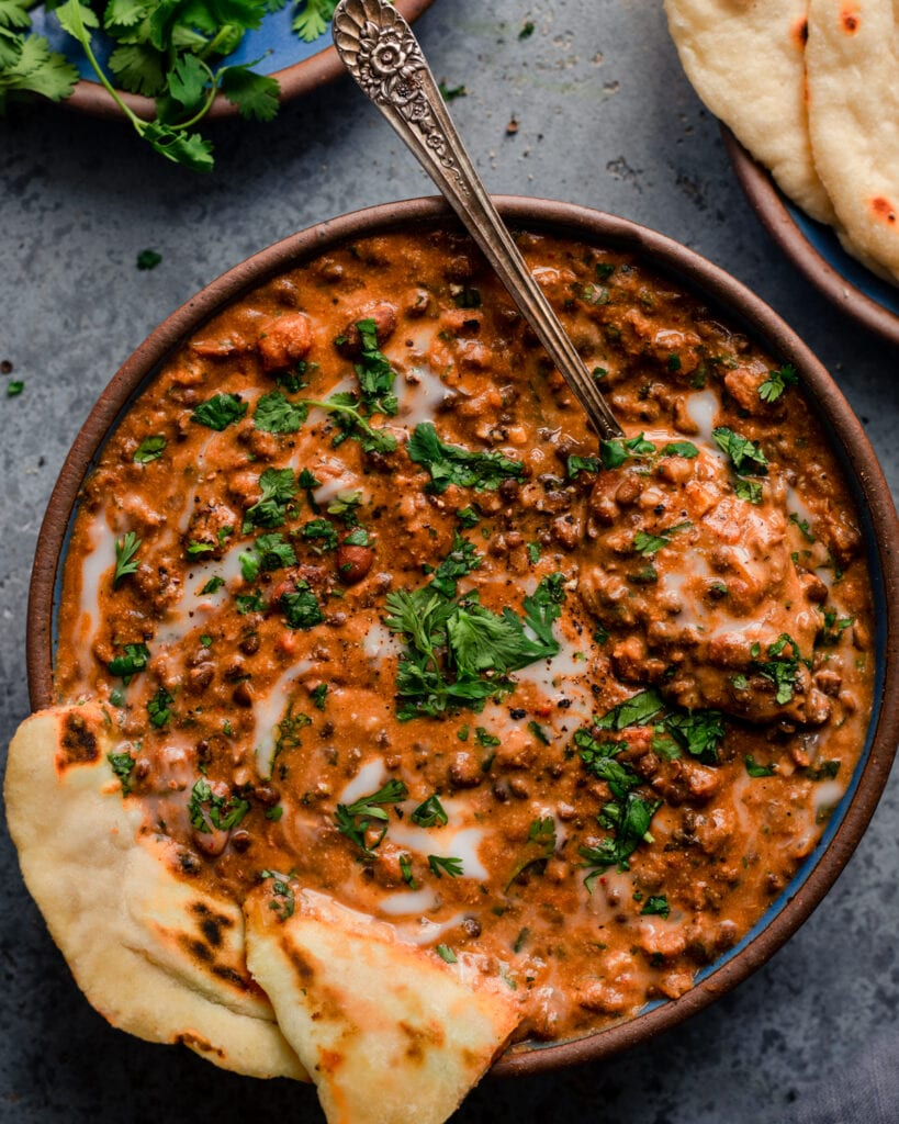 bowl of creamy vegan dal makhani with spoon and naan on blue background