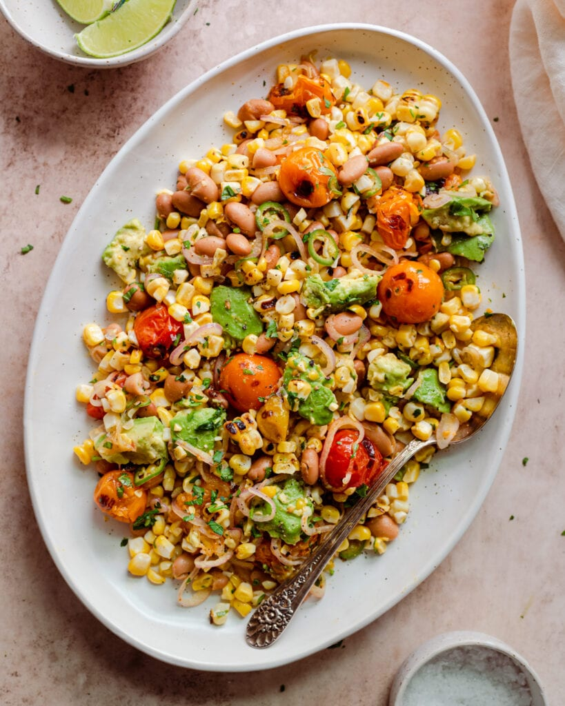 grilled corn salad with cherry tomatoes and avocado on serving platter with spoon