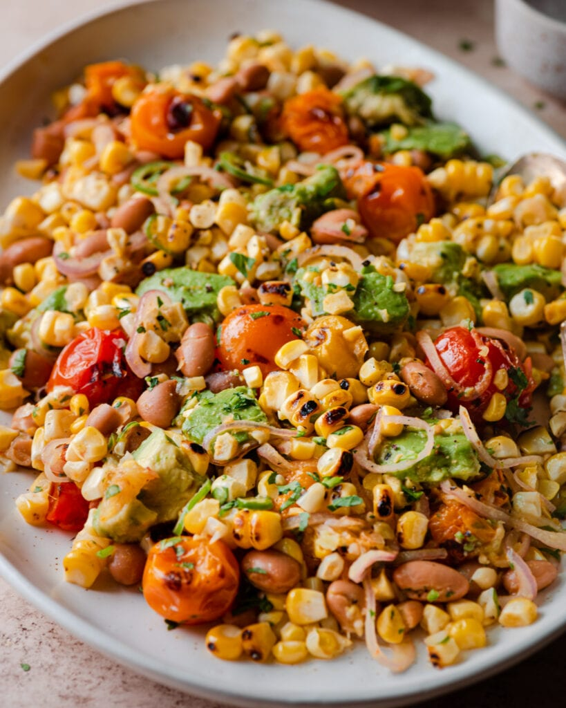 closeup photo of grilled corn salad on white platter
