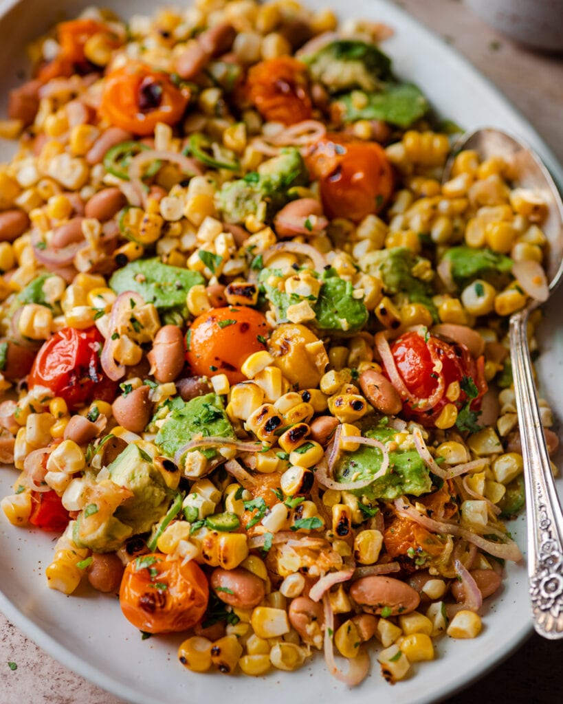 grilled corn salad with cherry tomatoes and avocado on serving platter