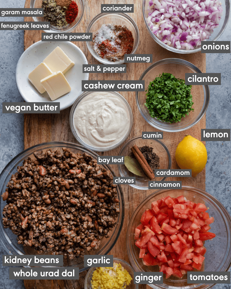 ingredients for vegan dal makhani on a cutting board with ingredients written in text
