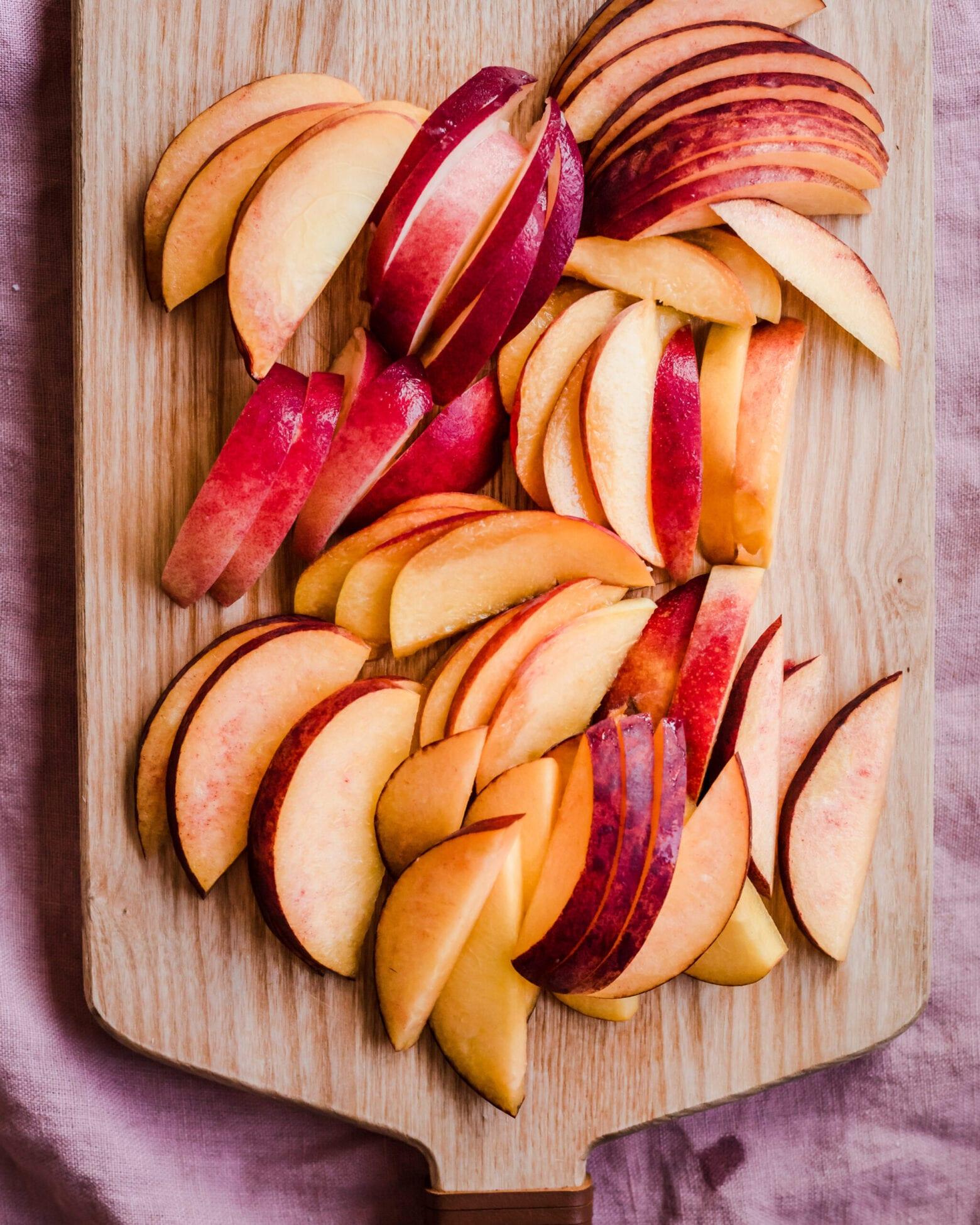 sliced peaches on cutting board