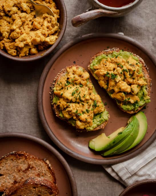 vegan tofu scramble on top of avocado toast on plate with side of tofu scramble on the side