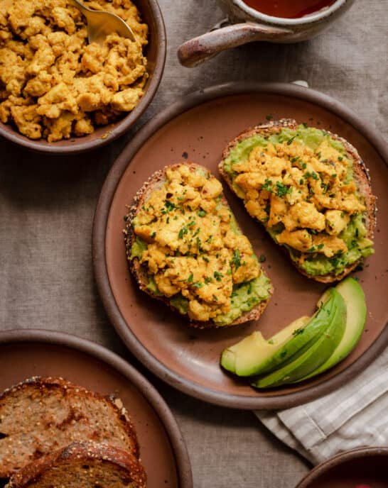 tofu scramble on avocado toast on a plate in a breakfast scene