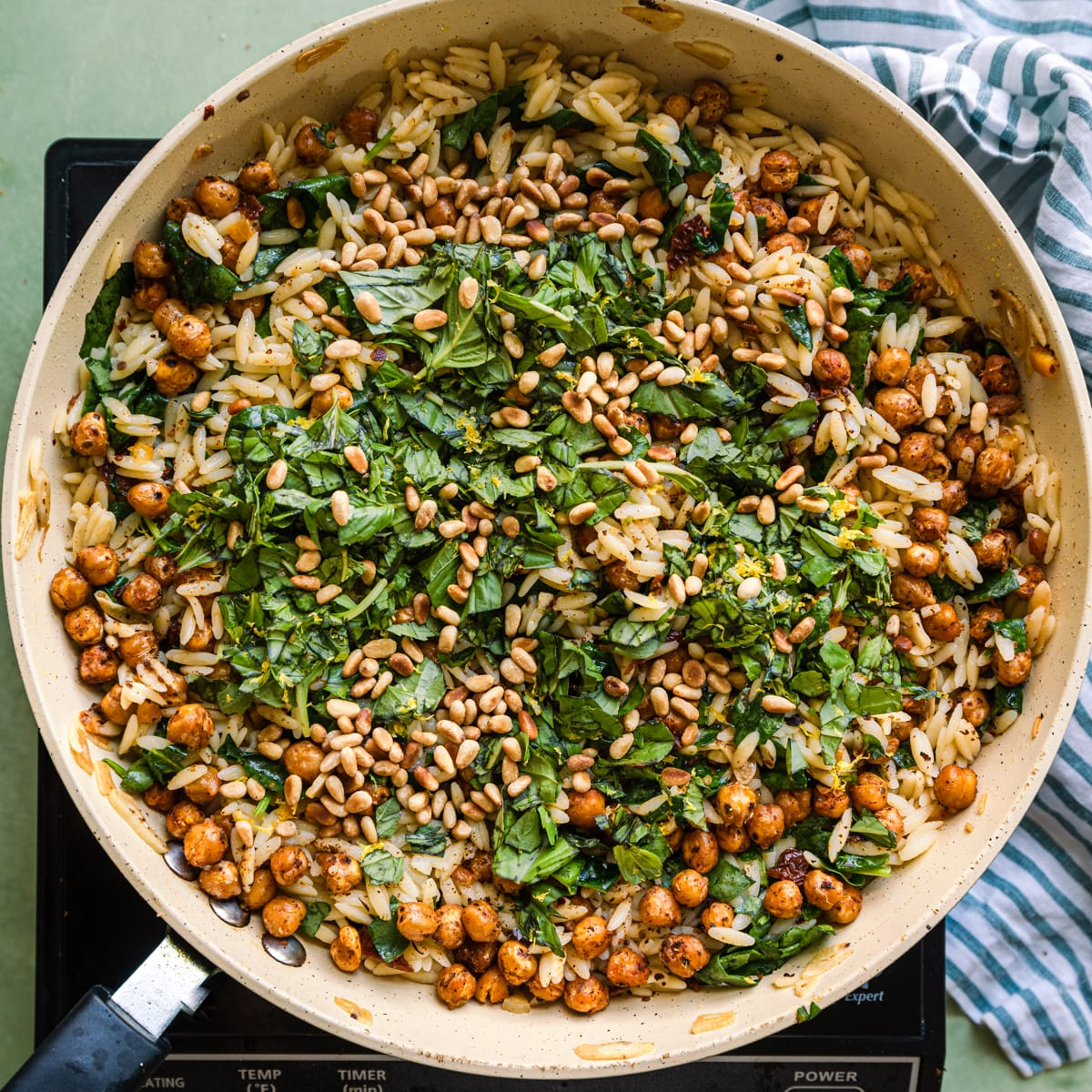 lemon orzo pasta salad in saute pan with fresh basil and pine nuts on top