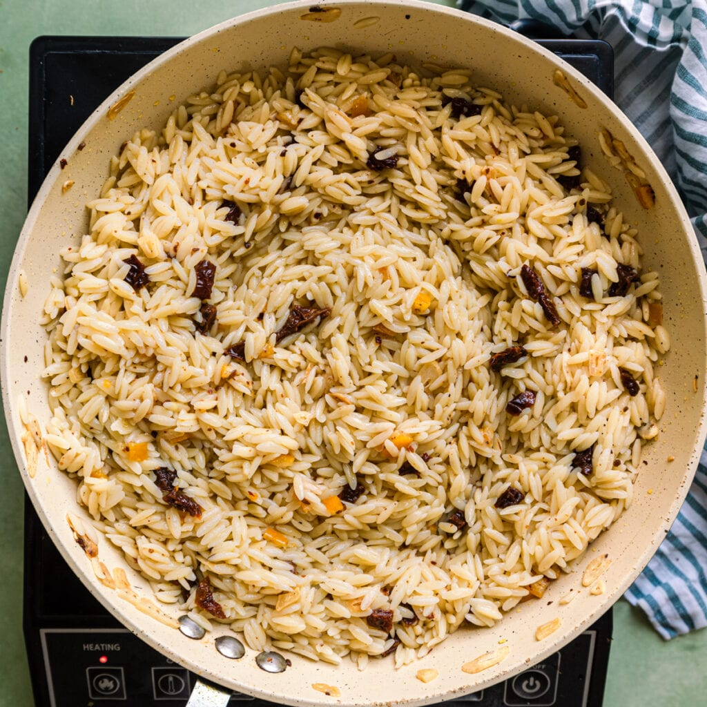 cooked orzo, sundried tomatoes and preserved lemons in saute pan with olive oil and garlic