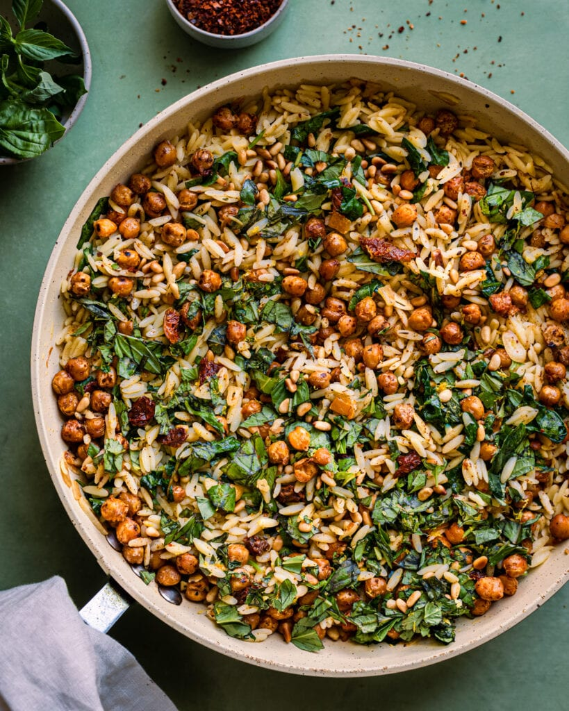 lemon orzo pasta salad with chickpeas in saute pan on green surface