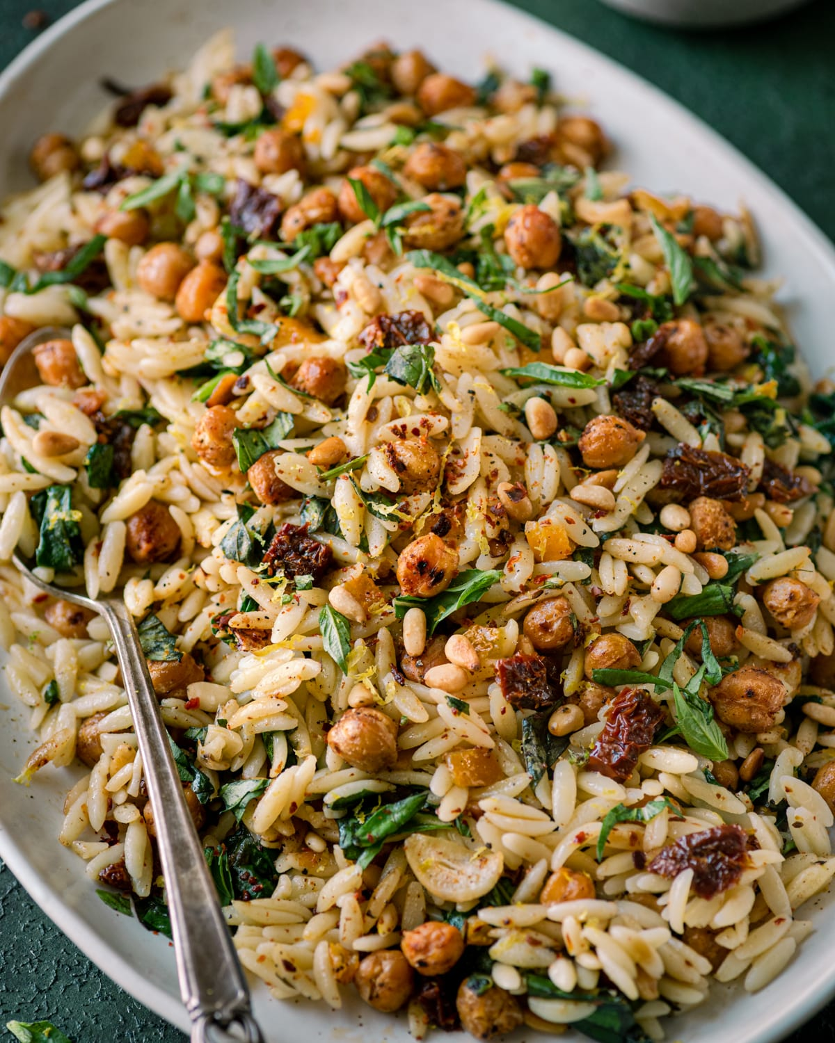 closeup of lemon orzo pasta salad on a tray with a spoon