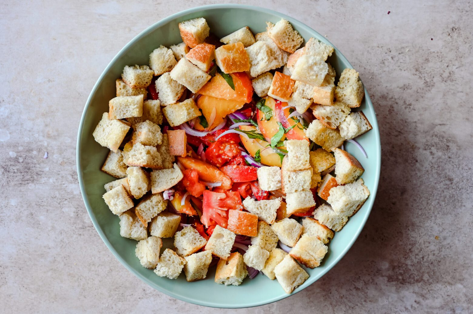 toasted bread cubes with sliced peaches, tomatoes, onions, and basil in a large bowl for panzanella salad