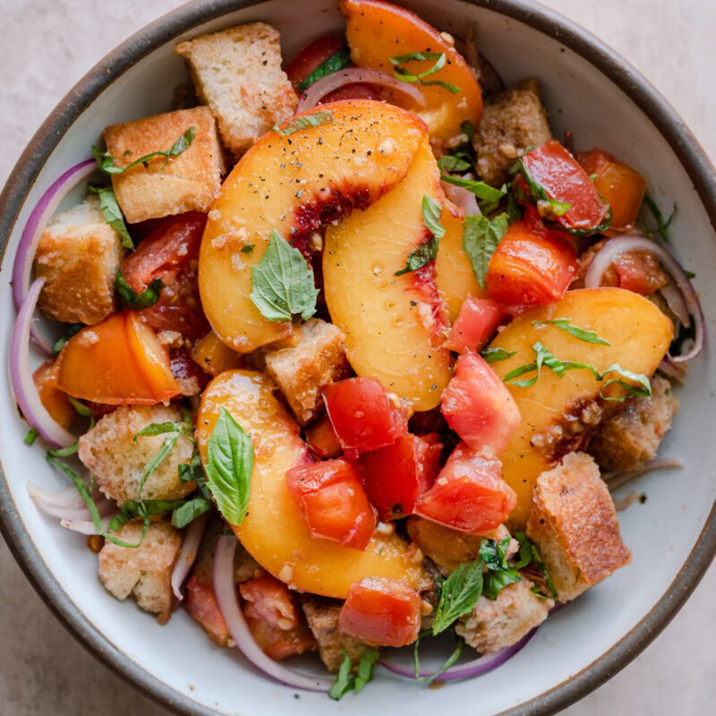 peach panzanella salad in a white bowl on a pink surface