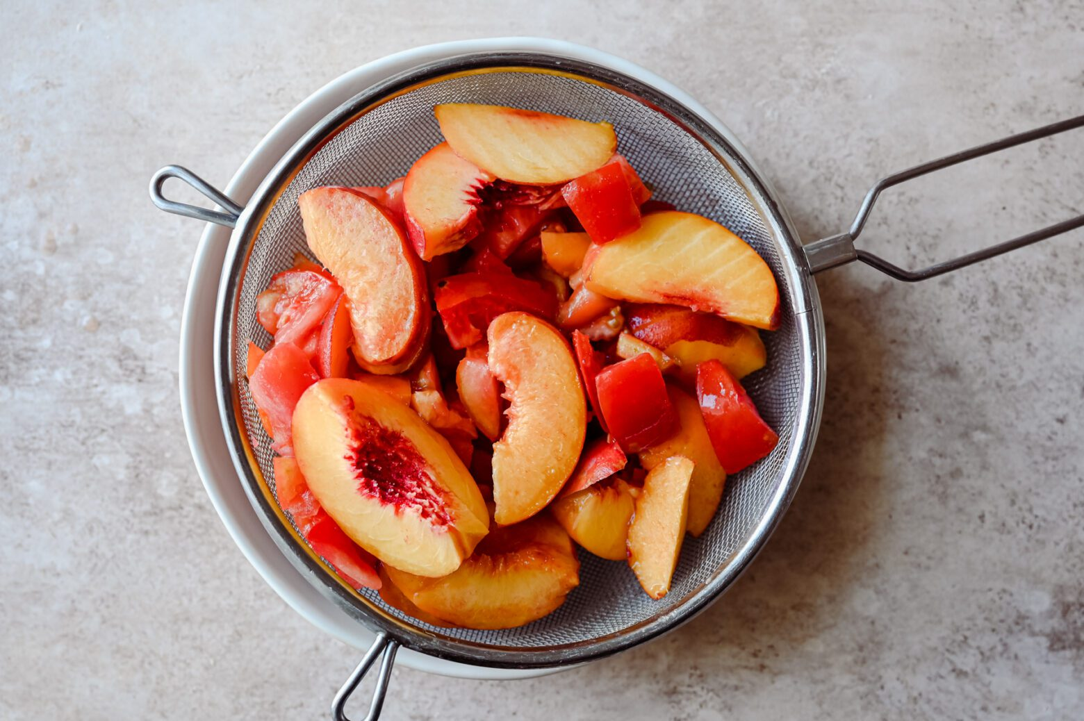 sliced peaches and tomatoes in colander