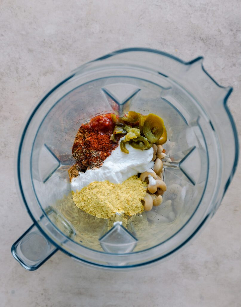 cashews, salsa, yogurt, spices, and nutritional yeast in a blender in blender