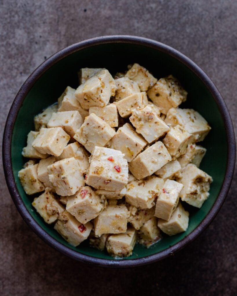vegan feta made from tofu in a green bowl