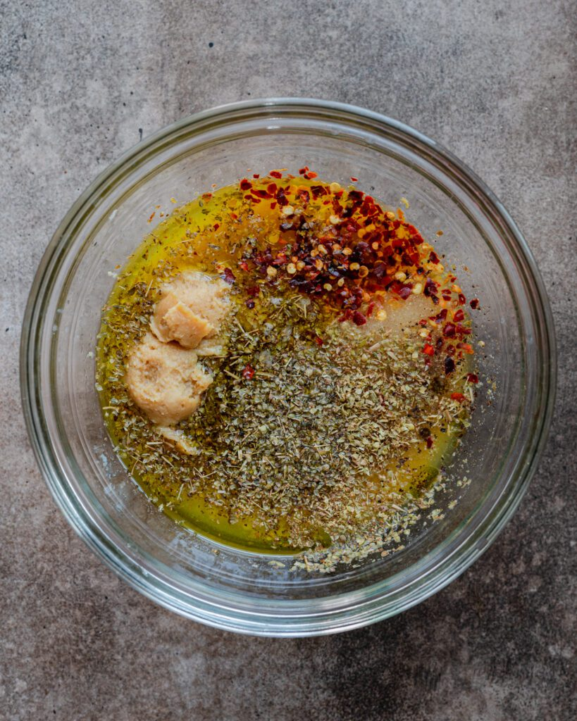 ingredients for the marinade to a medium bowl: miso paste, apple cider vinegar, olive oil, lemon juice, garlic, nutritional yeast, spices, and salt/pepper