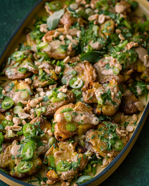 crispy smashed potatoes with ginger-tahini dressing, scallions, fresh herbs