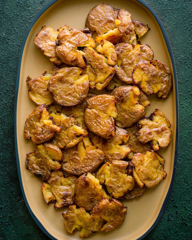 crispy smashed potatoes on yellow rimmed platter