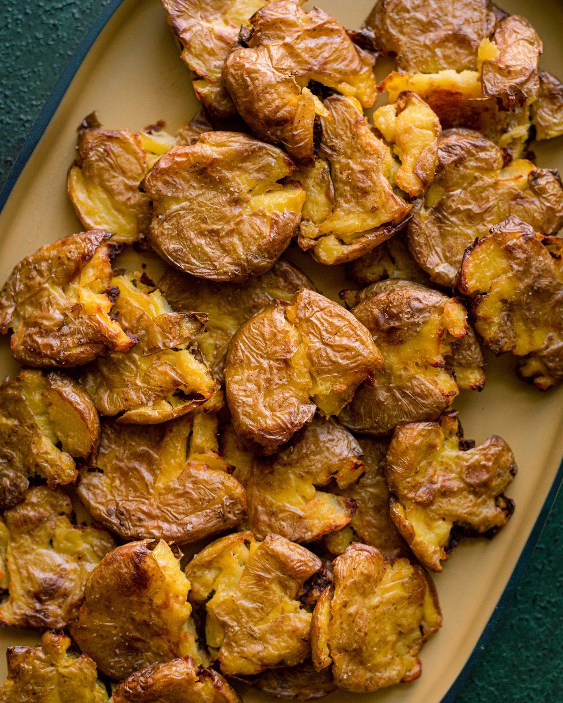 closeup of crispy smashed potatoes on a yellow platter