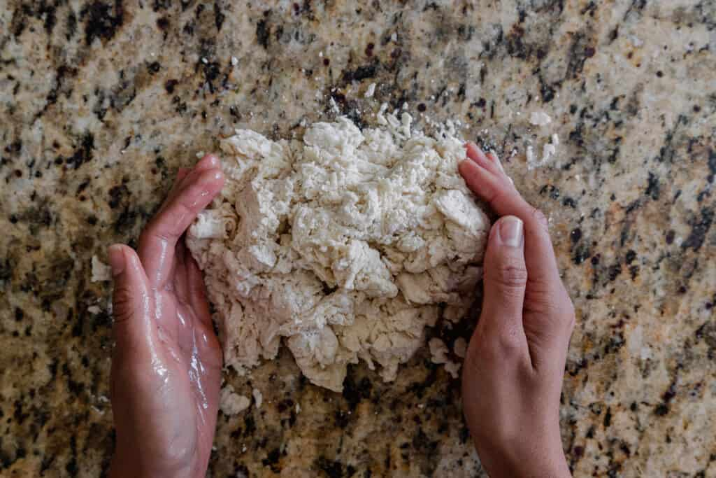 woman's hands about to knead a shaggy dough