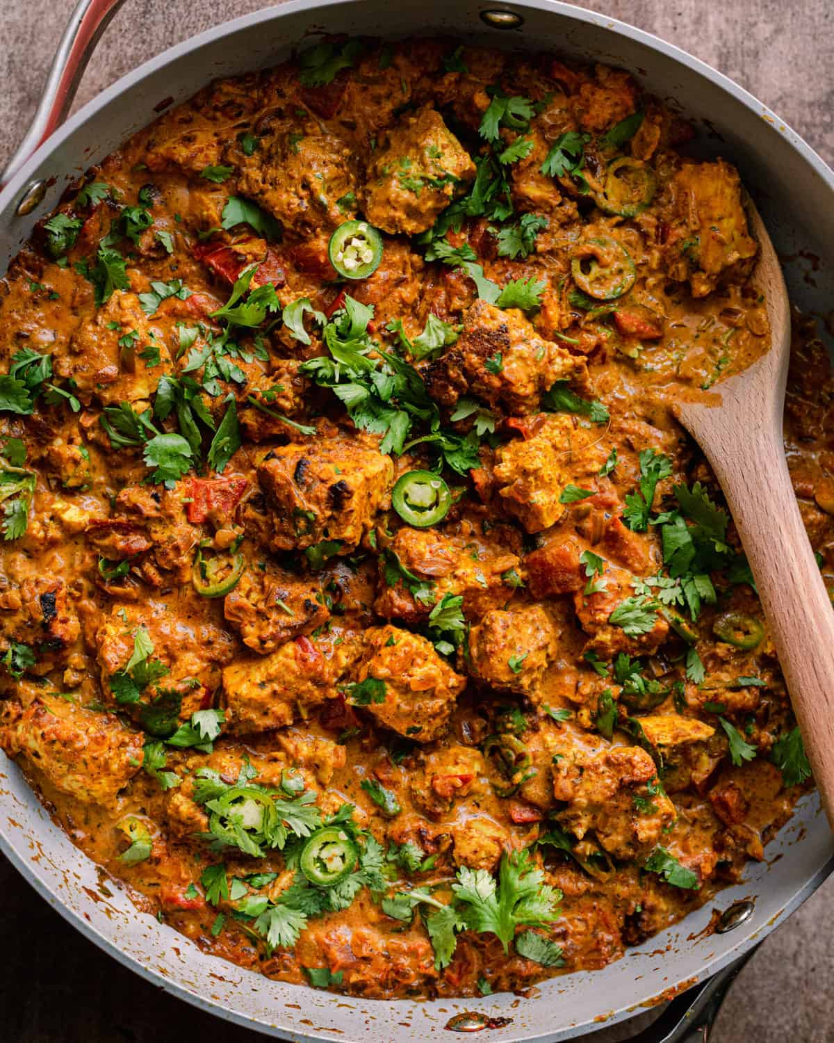 tofu tikka masala in a saute pan, garnished with cilantro and green chili peppers