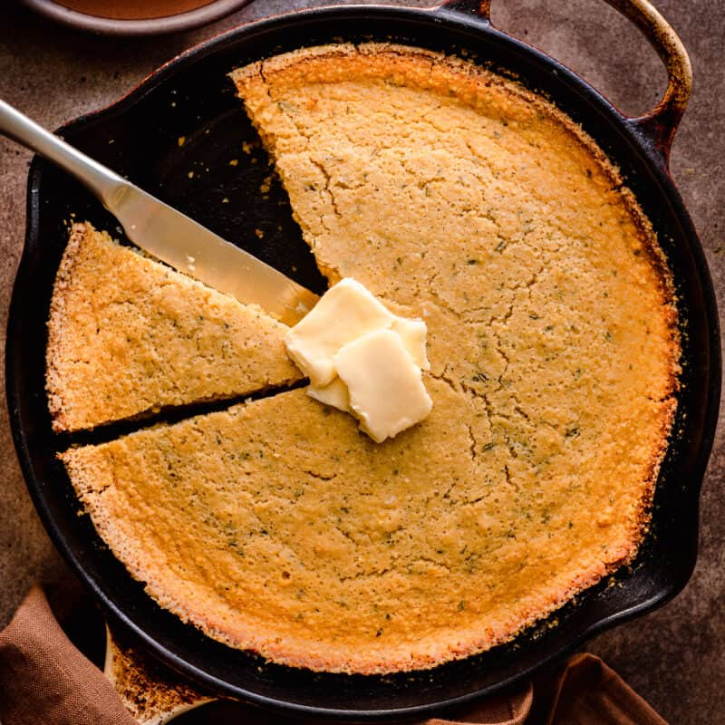vegan cornbread in a cast iron skillet with a slice taken out and vegan butter on top