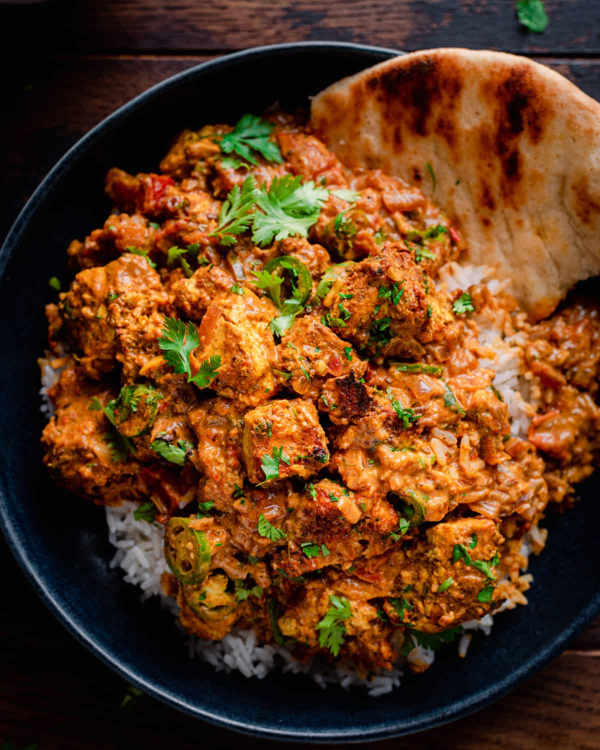 tofu tikka masala served over rice with naan in a bowl