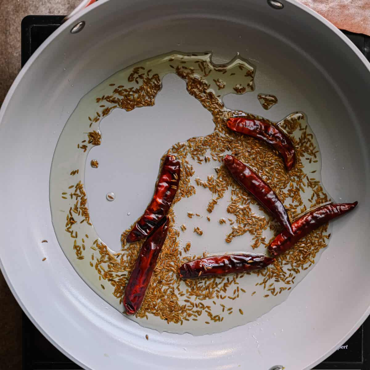 cumin seeds and dried red chili peppers toasting in oil