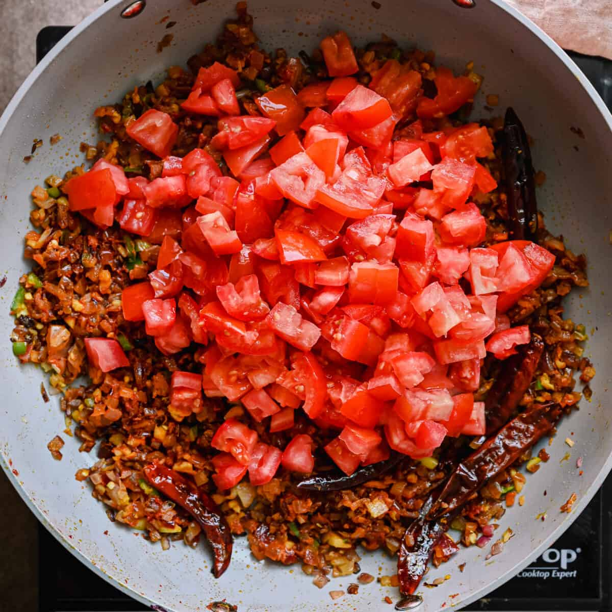 diced tomatoes sitting on top of masala in a saute pan