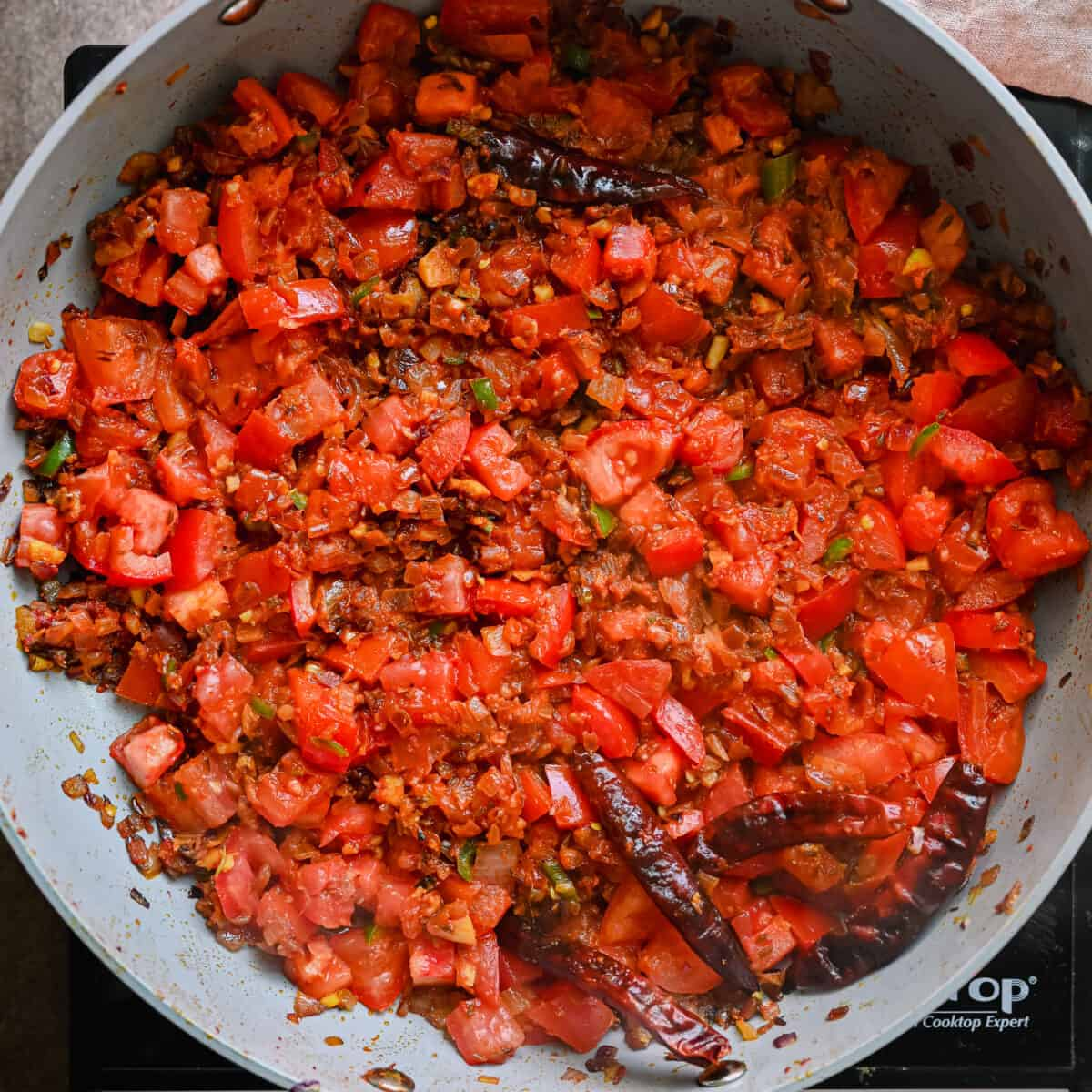 cooked tomatoes on top of masala in a saute pan