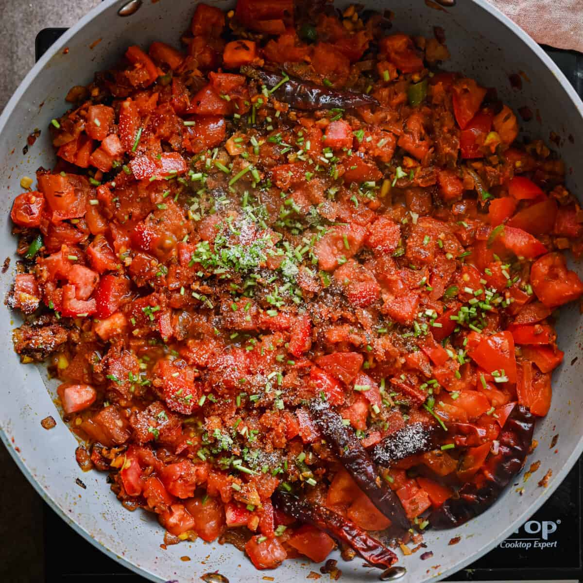 cooked tomatoes with cilantro on top of masala in a saute pan