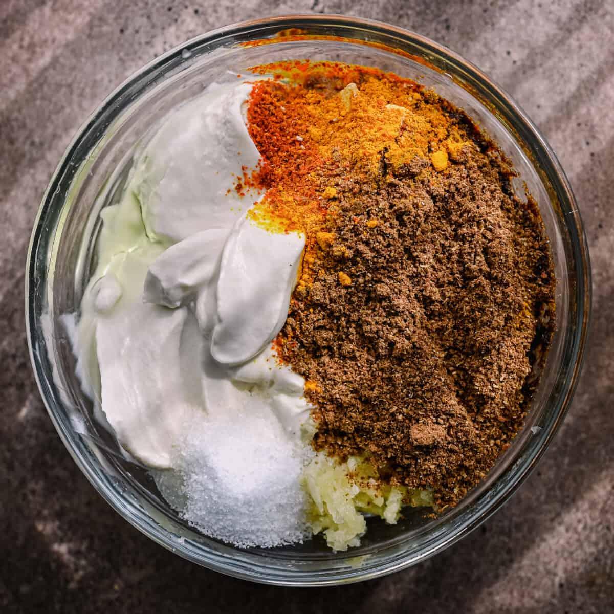 tofu tikka marinade with spices, yogurt, garlic, and ginger in a bowl