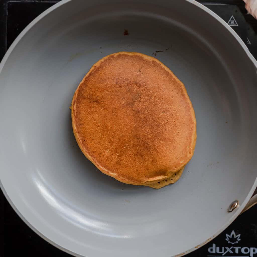golden pancake cooking in skillet
