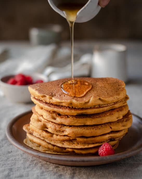 action shot of pouring maple syrup onto a stack of vegan pumpkin pancakes
